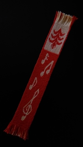 Woven bookmark in red and yellow, with musical notes, a treble clef and a pine tree